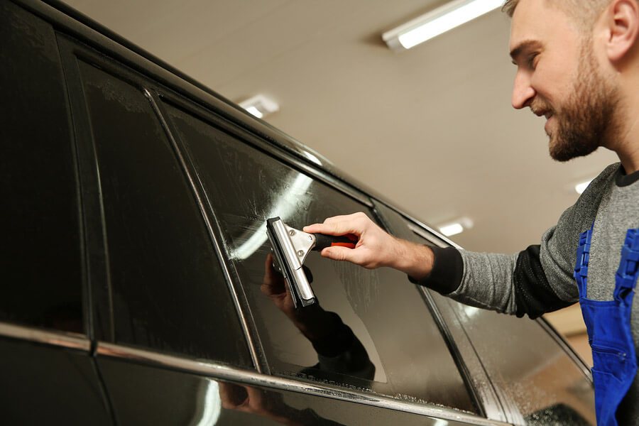 Worker removing tint from a limo and preparing the surface for re-tinting.